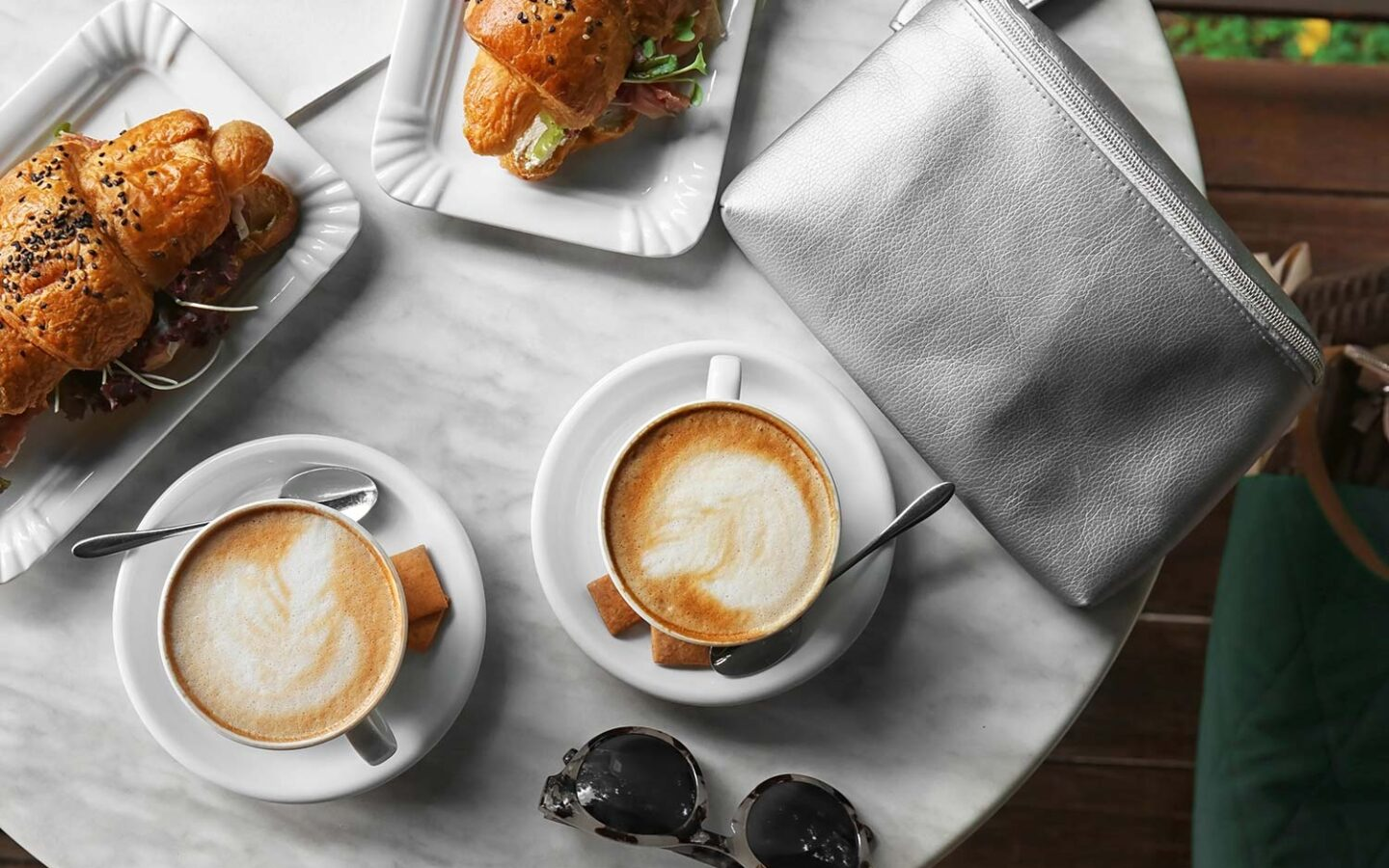 overhead view of a marble table with two cappuccinos and croissant sandwiches on top